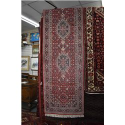 Wool carpet runner with multiple medallions, red background and overall floral design and highlights