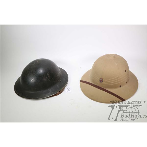 Two military hats including a Safari hat with Canadian General Service badge and a WWI helmet with l