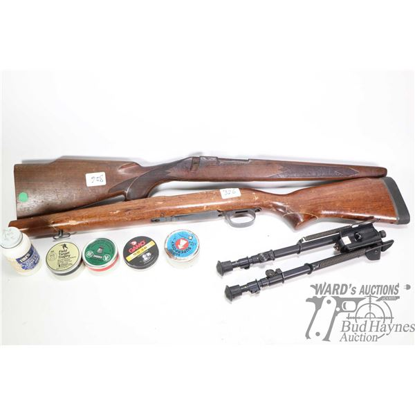 Two wooden gun stocks, a bipod and five containers with .22 pellets, three are full and unopened