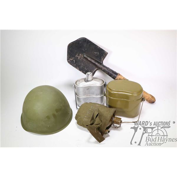 Selection of military supplies including metal helmet, small shovel, water canteen in canvas pouch a