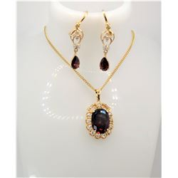 25)  GOLD TONE, CLEAR AND GARNET RED OVAL
