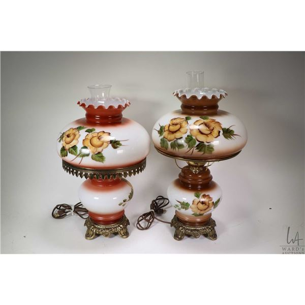 "Two electric ""oil lamp style"" table lamps with cast bases, clear hurricanes and hand painted shades"