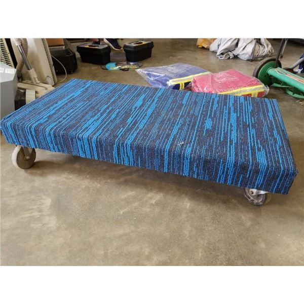 4 foot long blue carpeted four-wheel dolly
