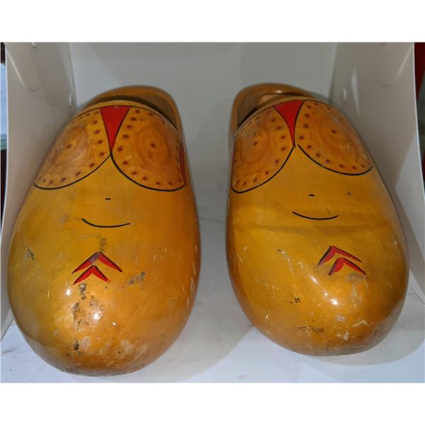 A pair of wooden shoes with mini vases