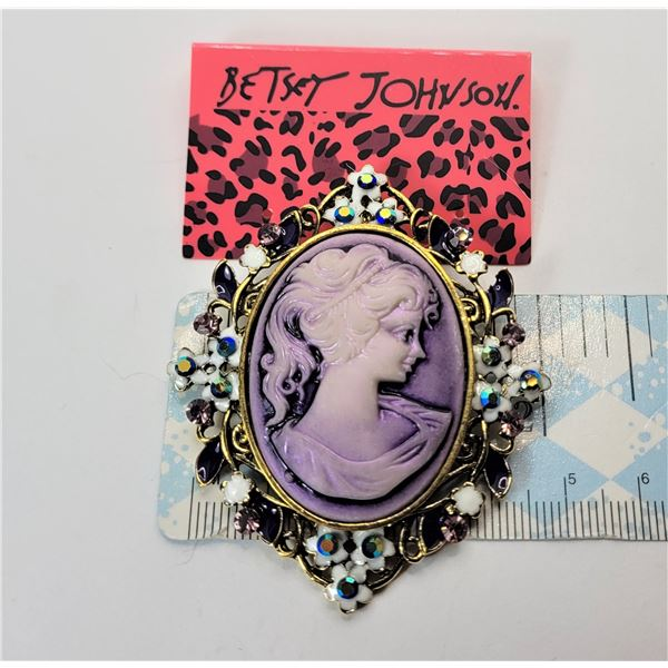 8)  BY DESIGNER BETSEY JOHN MAUVE CAMEO GOLD TONE BROOCH WITH WHITE ENAMEL AND CRYSTAL ACCENTS.
