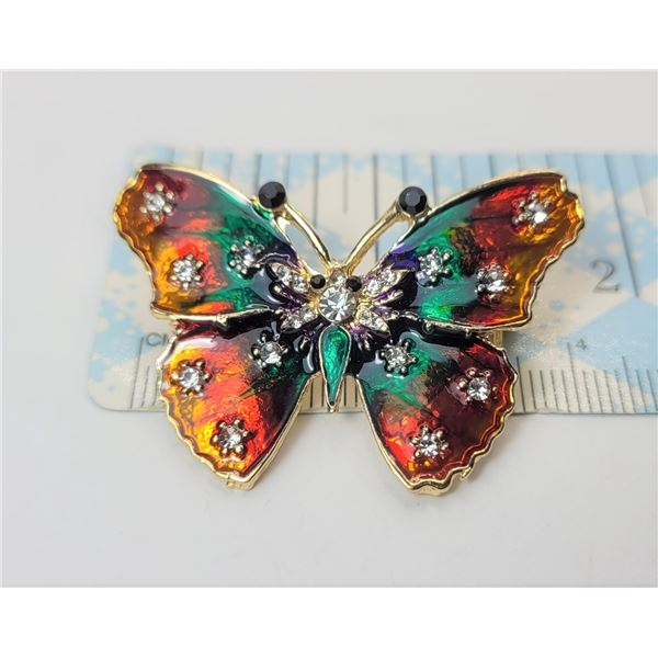 17)  GOLD TONE WITH MULTI COLORED ENAMEL AND CLEAR & BLACK CRYSTAL BUTTERFLY BROOCH.