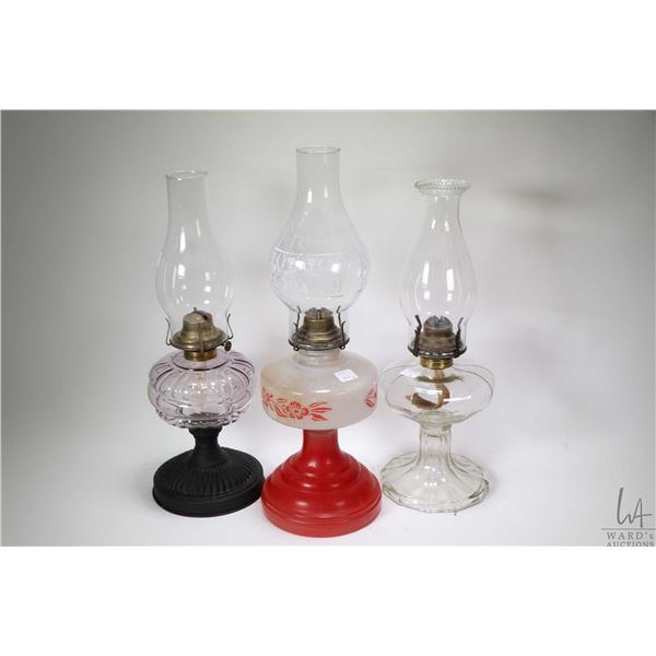 Six vintage oil lamps including four colourless with hurricanes, a colourless with a tin base and wh
