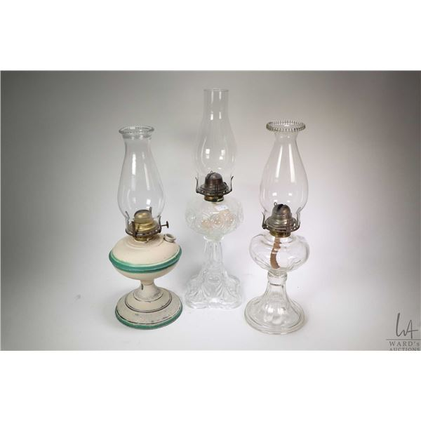Six vintage oil lamps including three colourless, a nickel plated lamp, a painted tin and a green gl