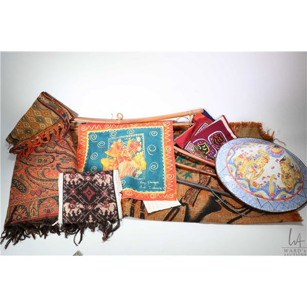 Selection of wall hangings and textiles including needlework, painted panels and an Asian hand paint