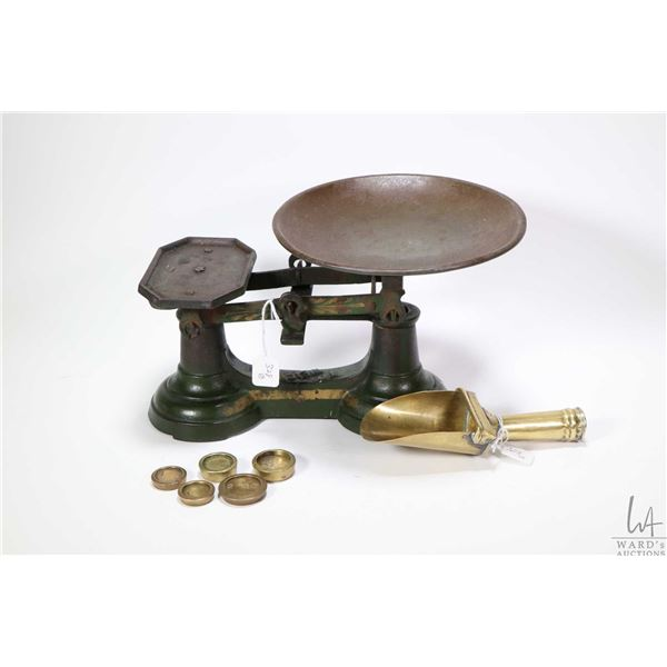 Antique cast balance scale, five brass weights and a brass sugar/ candy scoop