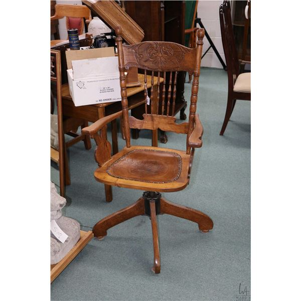 Pressed back swivel arm chair with decorative spindles and tooled leather seat