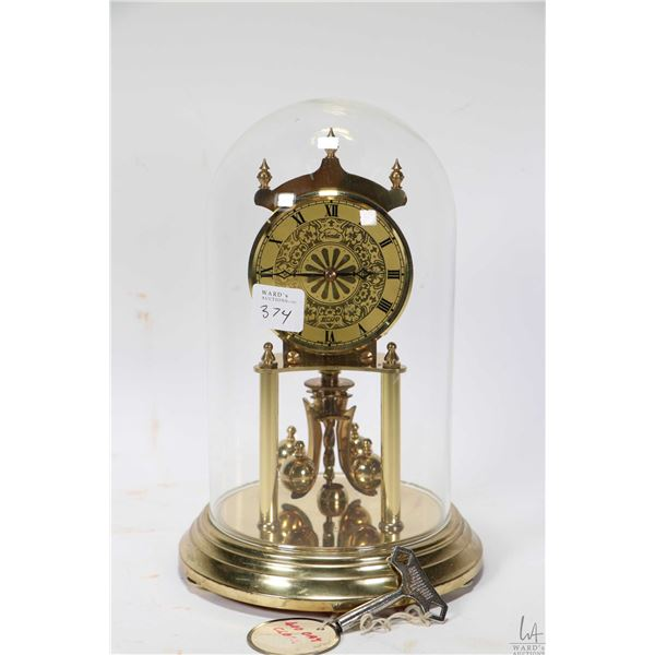"""Small dome to Kundo anniversary clock with glass dome 9"""" in height, working at time of cataloguing."""