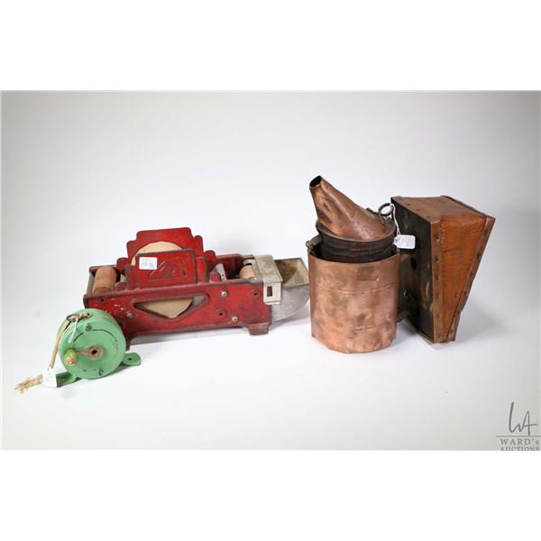 Vintage copper bee smoker with leather bellows, a cast metal gummed paper dispenser and a Tala retra