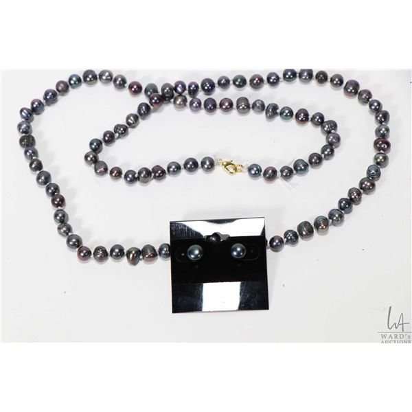 Strand of individually knotted blackish purple and green gray fresh water pearl necklace with gold t