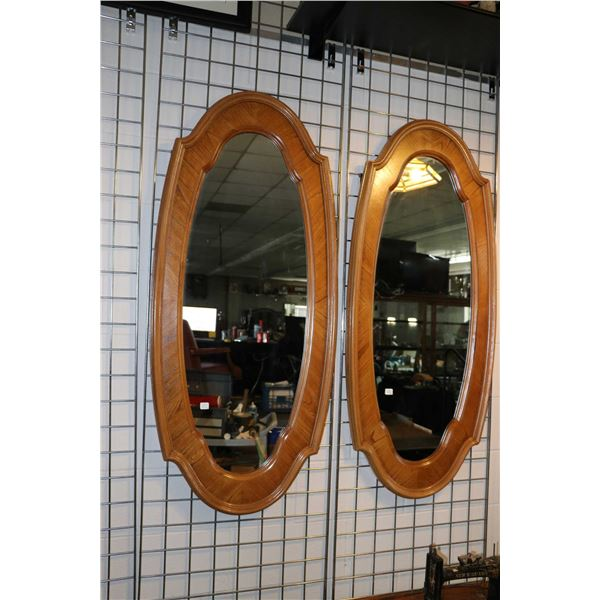 """Pair of semi contemporary wood framed oval wall mirrors, overall dimensions 52"""" X 23"""". Not Available"""