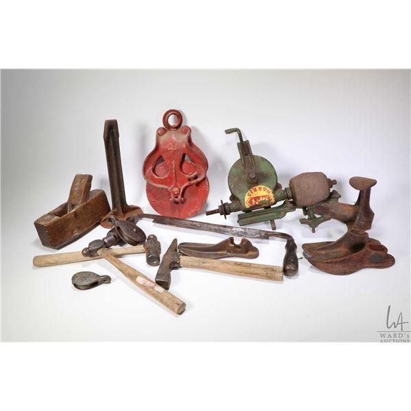 Selection of vintage tools including Massey-Harris grinding wheel, vintage wooden pulley, wooden blo