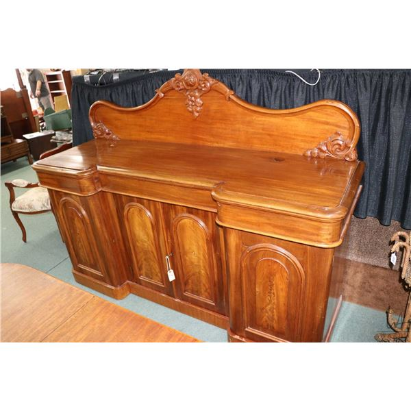 Antique Victorian mahogany sideboard with scroll and floral motif backboard, four raised panel doors