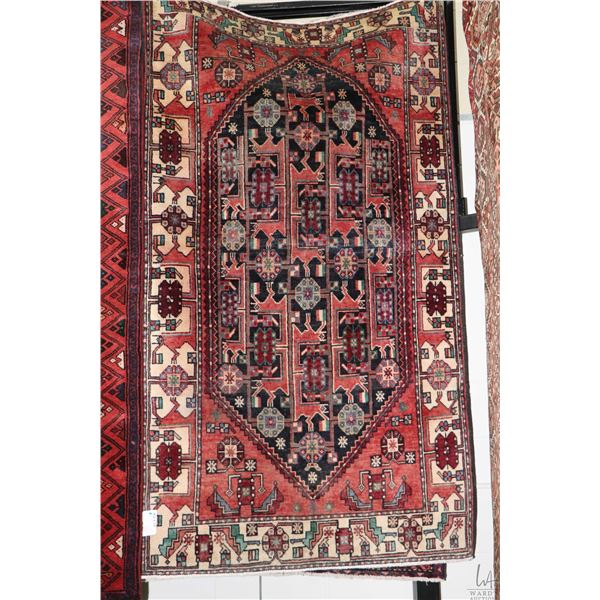 100% Iranian Baloochi area carpet with center medallion, red background and highlights of blue, gree