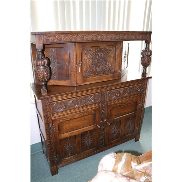 Antique oak three door, two drawer court cupboard with Tudor style raised panel doors and carved dec