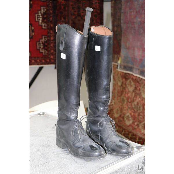 A pair of ladies English riding boots, size 7.5 US with wood handled strap tightener and riding crop