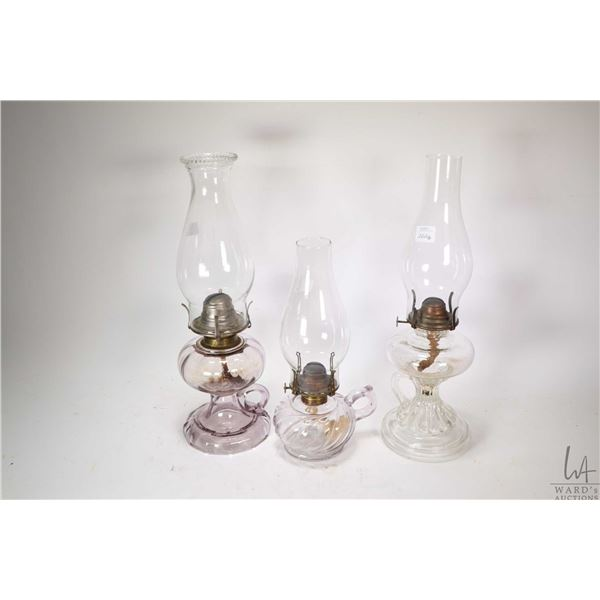 Three colourless oil lamps including two turning purple