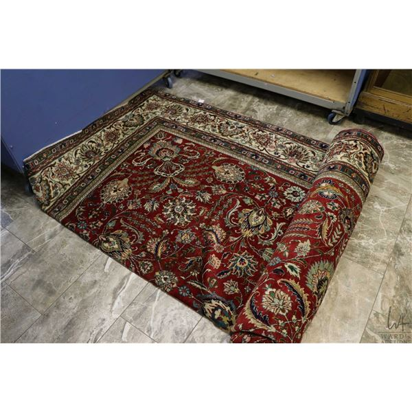 100% Iranian hand made area carpet with red background, overall floral pattern and highlights of cre