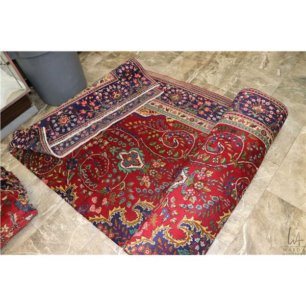 100% Iranian area carpet with red background, purple borders and highlights of green, brown, cream e