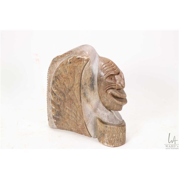Hand carved soapstone of an eagle head and a face with head dress signed by artist Travis Thomas '85