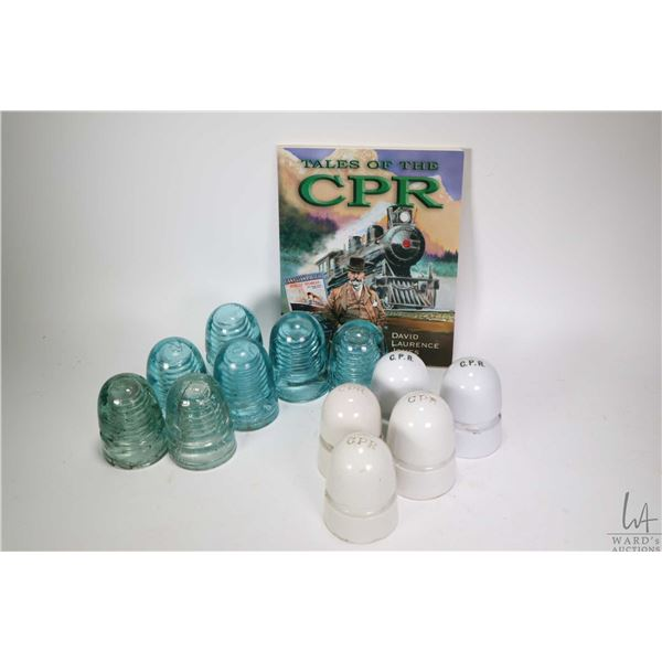 """Twelve vintage insulators including five CPR ceramic and seven glass plus a volume of """"Tales of the"""