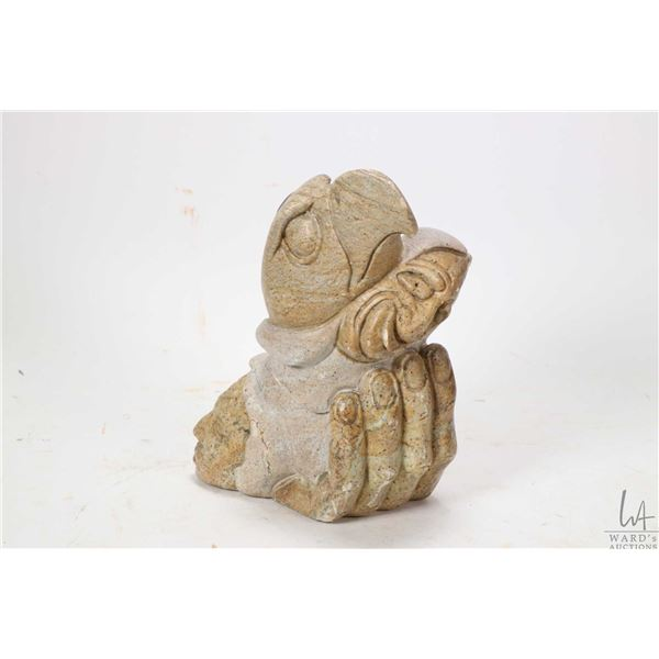 """Hand carved soapstone featuring a hand holding an eagle head and two human heads 7 1/2"""" in height an"""