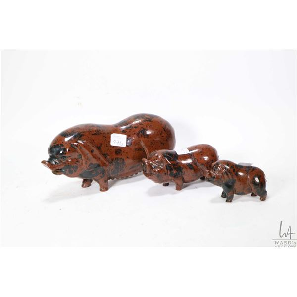 Three carved pigs ranging from 3 1/2  to 9