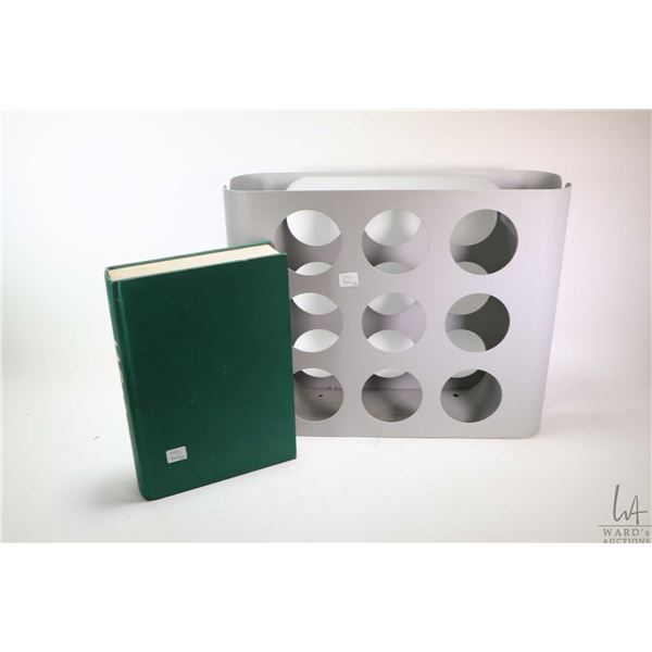 """Stamped steel nine hole wine rack and a hardcover copy of """"Wine"""" by Andre Domine"""