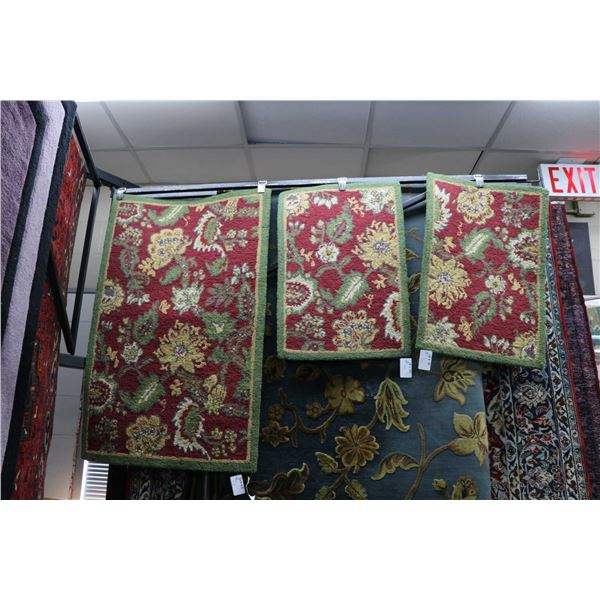 Three small scatter rugs with green borders and floral design, red backgrounds and shades of yellow,