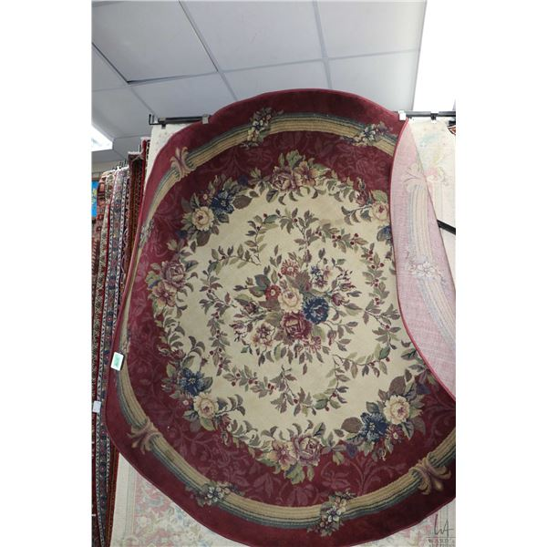 Round area carpet with floral center medallion, sand and cranberry background and highlights of blue
