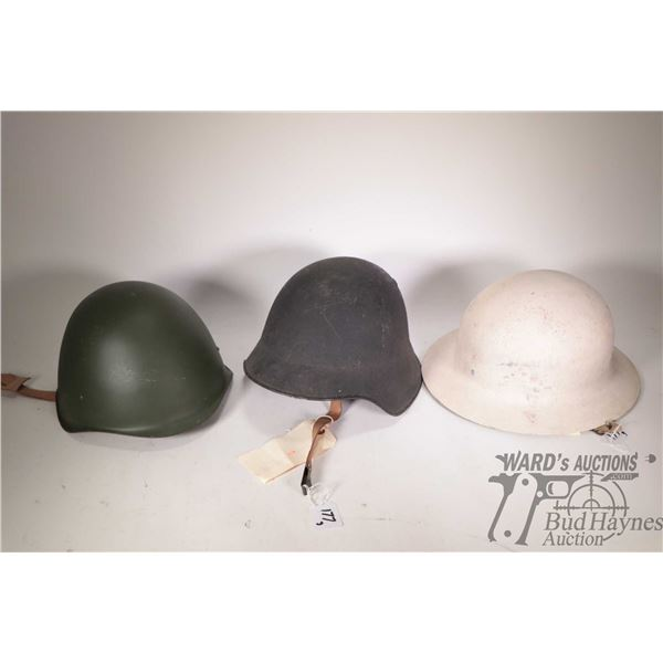 Three vintage military helmets including a Swiss M40/43, Swiss Military Civil Defense and a Hungaria