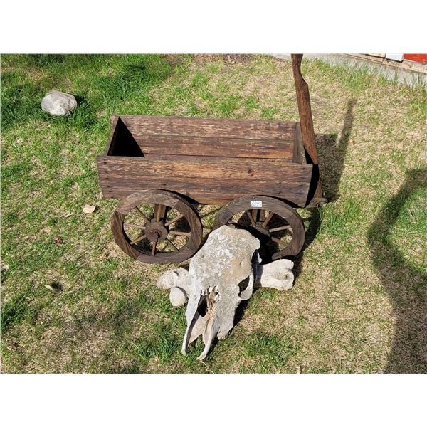 Wooden wagon garden planter with a cow skull and bone.