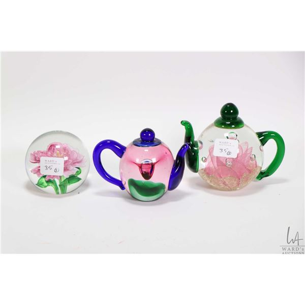 Three collectible glass paperweights by Edinburgh Glass including two teapot shaped and a cased glas