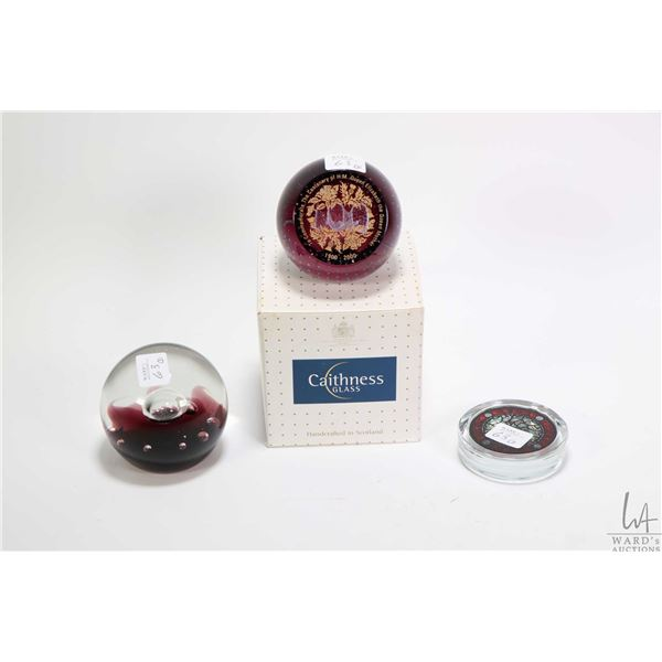 """Three collectible glass paperweights including Caithness Glass """"To Commemorate the Centenary of H.M."""