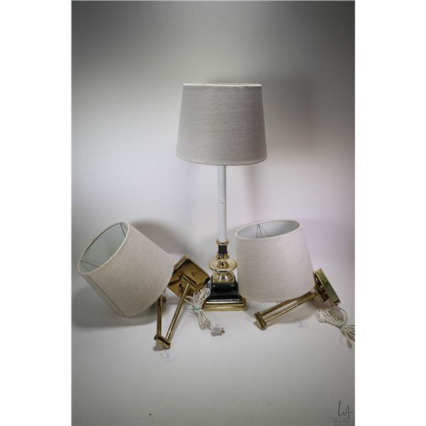 Pair of brass toned pivoting wall mount electric sconces with shades plus a table lamp