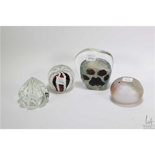 Four collectible glass paperweights including cased glass, artist signed pieces including Moon Tan a