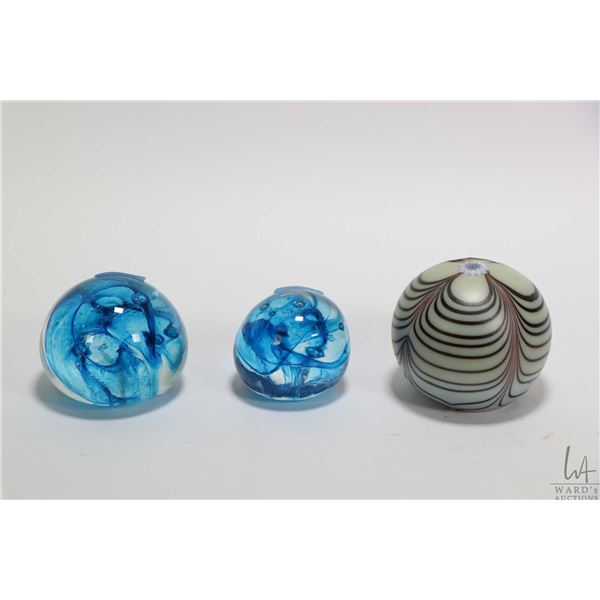 Three collectible glass paperweights, all appear unsigned