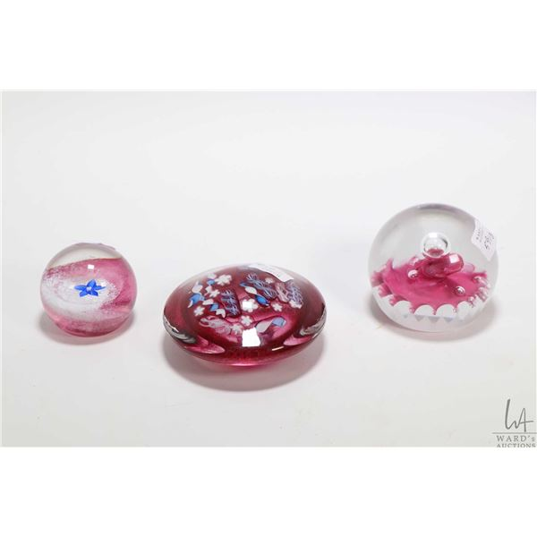 Three collectible glass paperweights including Caithness, one artist signed V. Wilson and one marked