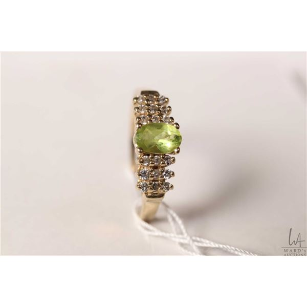 10kt yellow gold ring set with oval peridot like gemstone and diamond accents, size 7.25