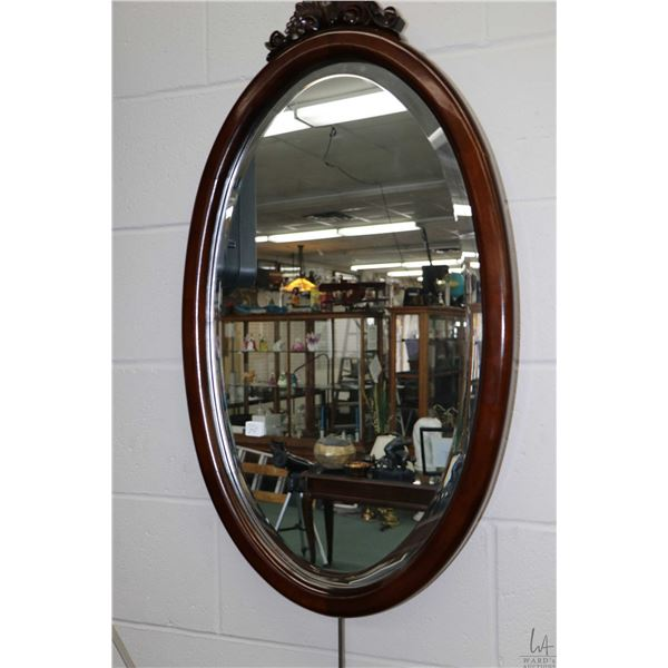 """Wood framed oval bevelled wall mirror with carved decorative topper, overall dimensions 33"""" X 19"""". N"""