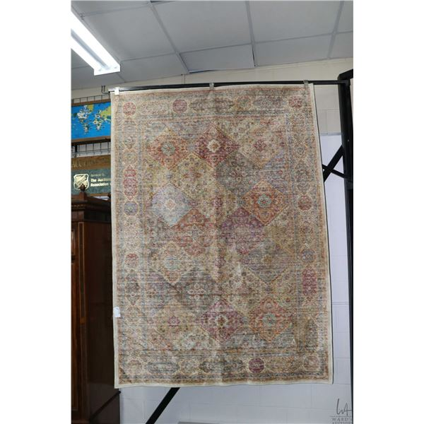 100% viscose Sevila area carpet in ivory tones with patch work diamond patterning and multiple borde