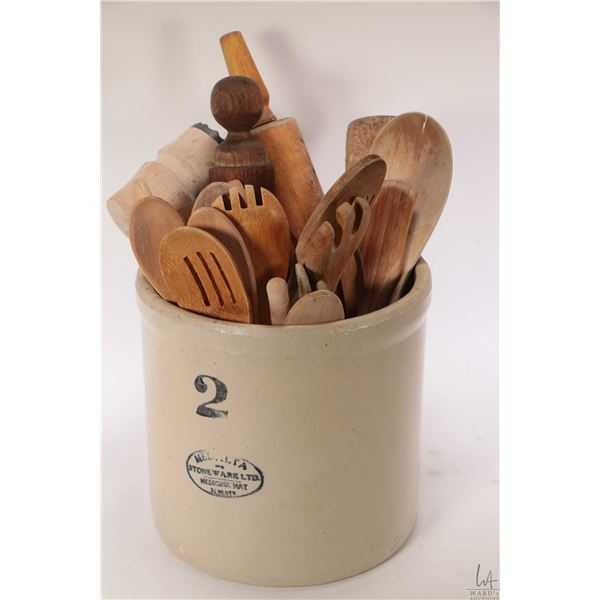 Two gallon Medalta stoneware crock with a large assortment of wooden kitchen utensils including spoo