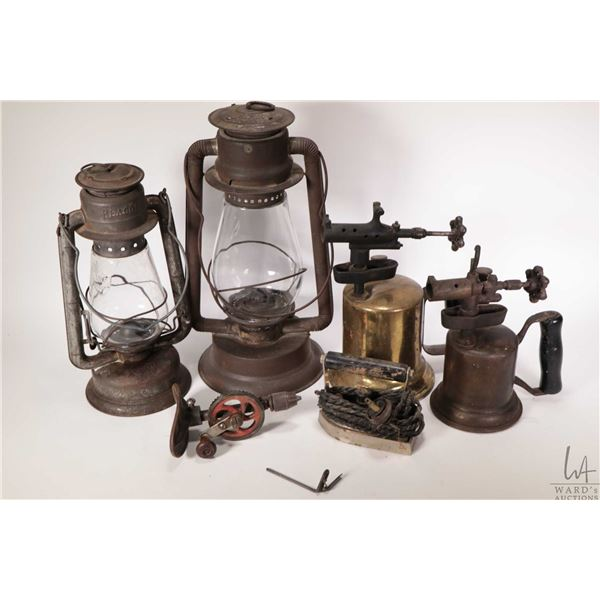 Two barn lanterns, two metal torches, a palm hand drill and a small electric iron