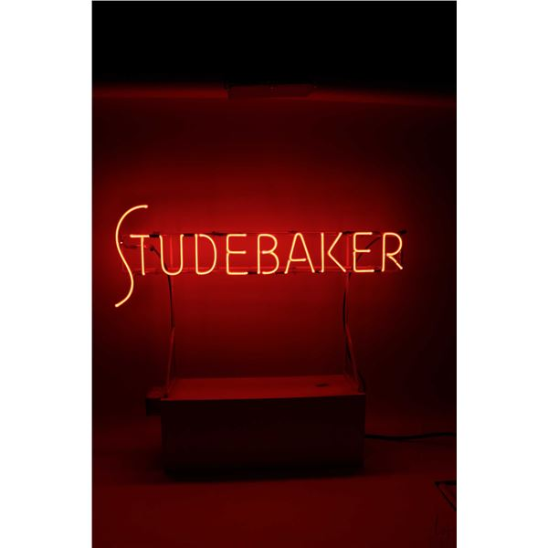 """Vintage Neon Studebaker sign, working at time of cataloguing, 35"""" in length and 29"""" with stand. Note"""