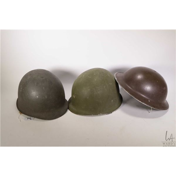 Three military helmets including Canadian WWI style and two American style, one with fiberglass line