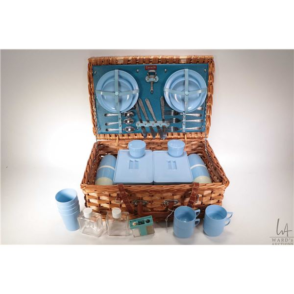Vintage woven wicker picnic basket with settings for four of luncheon plates, cups and saucers and b